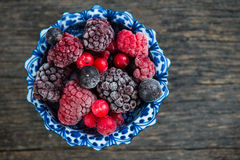 Mixed frozen berries on wooden background Stock Photography