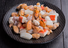 Mixed frozen seefood. Mixef frozen seafood on black plate and black background Royalty Free Stock Photo