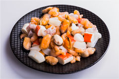 Mixed frozen seefood. Mixed frozen seafood on black plate and white background Stock Photo
