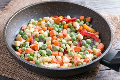 Mixed frozen vegetables in a frying pan on wood table Royalty Free Stock Image