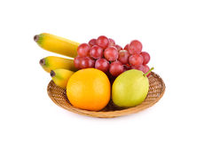 Mixed fruit, banana, orange, pear, grape in basket on white Royalty Free Stock Images