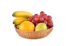 Mixed fruit, banana, orange, pear, grape in basket on white Stock Photo