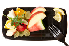 Mixed fruit on black plate Royalty Free Stock Photography
