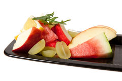 Mixed fruit on black plate Royalty Free Stock Photo