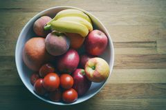 Mixed fruit bowl on wood background Royalty Free Stock Photos
