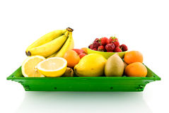 Mixed fruit on green tray. Isolated on white background stock images