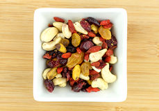 Mixed fruit and nuts in white bowl on wooden background Stock Image