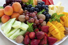 Mixed fruit platter. With strawberries, mango, cantaloupe, grapes, apricots, walnuts and mint Stock Image