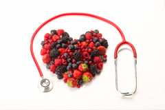 Mixed fruit with a stethoscope. Mixed fruit in the shape of a heart with a stethoscope, placed on a white background Stock Images
