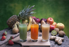 Mixed fruit on a wooden board with juice Royalty Free Stock Photos
