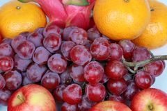 Mixed fruits as Red seedless grapes,orange,apple,Dragon fruit,Ja. Food for health,Mixed fruits as Red seedless grapes,orange,apple,Dragon fruit,Japanese golden Stock Image