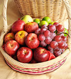 Mixed fruits in the basket. Apples and grapes in the basket Stock Photo