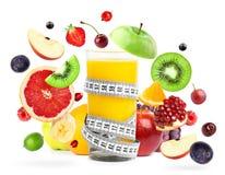Mixed fruits falling and orange juice Stock Image