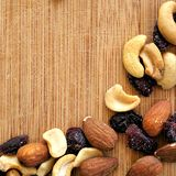 Mixed fruits and nuts on wood grain cutting board, arranged in square image for social media, banners, and backgrounds. stock image