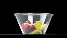 Mixed fruits salad in glass bowl, stop motion time lapse on black background, healthy dessert stock footage