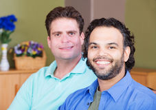 Mixed Gay Male Couple. Latino and Caucasian gay men sitting together Stock Images