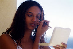Mixed girl at make-up. A young mixed woman's making-up her eyes Royalty Free Stock Images