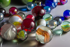 Mixed Glass Marbles. Closeup view of translucent marbles on a shiny surface Royalty Free Stock Images
