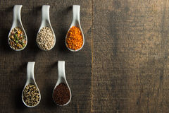 Mixed grains in white spoons on wood Royalty Free Stock Image