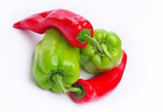 Mixed Green and Red Peppers. Two large green red peppers and two long red peppers Royalty Free Stock Image