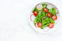 Mixed green salad with fresh spinach, radish and cherry tomatoes. Slices and olive oil Royalty Free Stock Photo