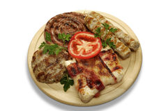 Mixed grill of pork. On a wooden mat stock photo