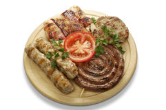 Mixed grill of pork. On a wooden mat Royalty Free Stock Image