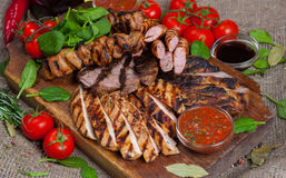 Mixed grilled meat platter. Assorted delicious grilled meat with vegetable. royalty free stock photography