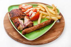 Mixed grilled meat served with tomato salad and french fries Royalty Free Stock Image