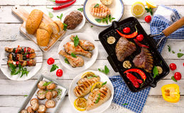 Mixed Grilled meats with vegetables on a white wooden table. Stock Photography