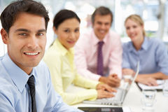Mixed group in business meeting on laptop. Smiling to camera Royalty Free Stock Photography