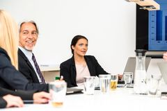 Mixed group in business meeting. With laptops, projection screen, digital tablets and smartphones discussing the latest sales figures Royalty Free Stock Photography