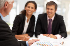 Mixed group of colleagues in business meeting. Mixed group in business meeting looking and discussing charts Royalty Free Stock Image