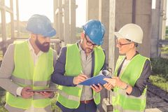 Group of architects or business partners having a meeting and signing documents on a construction site royalty free stock photography