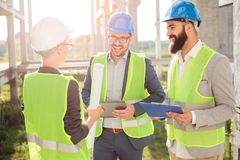 Group of young architects or business partners meeting on a construction site stock photography