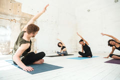 Mixed group of young people doing yoga class stock images