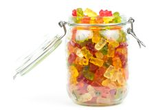 Mixed gummy bears / jelly baby candy sweets in an open jar. On a white background royalty free stock photo