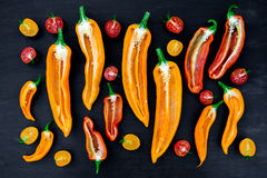 Mixed of half red and yellow pepper with a green branch near cherry tomato on  black backround. Top view. Stock Image