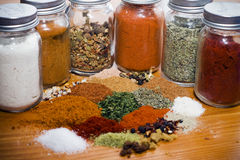Mixed herbs and spices on a wooden table surface. Assorted herbs and spices in glass containers Stock Image