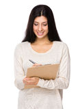 Mixed indian woman write on clipboard Stock Photos
