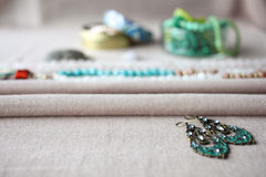 Mixed jewelery on grey cotton background: beads, earrings, rings, glass beads, necklace chain. Ethnic, turkish adornment in blue, grey and green colors Stock Photography