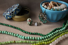 Mixed jewelery on grey cotton background: beads, earrings, rings, glass beads, necklace chain. Ethnic, turkish adornment in blue, grey and green colors Royalty Free Stock Photos