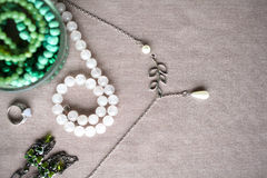 Mixed jewelery on grey cotton background: beads, earrings, rings, glass beads, necklace chain. (ethnic, turkish adornment in blue, grey and green colors Royalty Free Stock Photo
