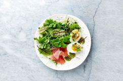 Mixed leaf salad with egg, serrano ham, and herbs. Healthy diet. Flat lay. Home made food. Healthy diet concept royalty free stock photography
