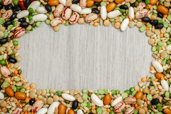 Mixed legumes and cereals. Mixed dried legumes and cereals arranged around grey wooden background. Copy space in middle Stock Image