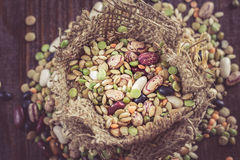 Mixed legumes and cereals. Mixed dried legumes and cereals in small burlap bag on dark wooden background Royalty Free Stock Photography