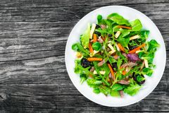 Mixed lettuce, spinach, carrot, ham, cheese and prunes salad , top-view.  Stock Photos