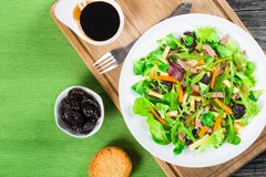 Mixed lettuce, spinach, carrot, ham, cheese and prunes salad , top-view Royalty Free Stock Photo