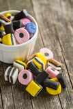 Mixed liquorice candies. Mixed liquorice candies on old wooden table royalty free stock image