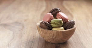Mixed macarons in wood bowl on table Stock Images